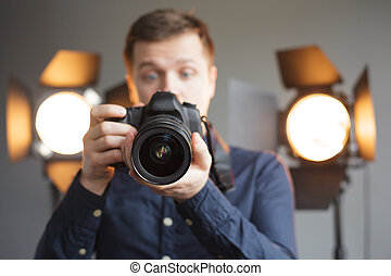 Man with a camera in the studio on the background lighting looks in screen with surprise