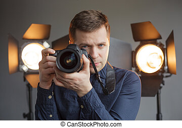 Man with a camera in the studio on the background lighting