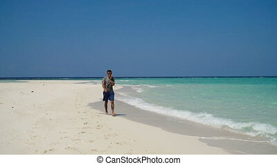 Man with a cell phone on the beach.