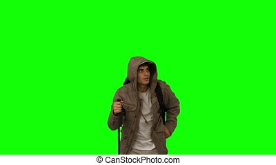 Man with a coat trekking on green screen in slow motion
