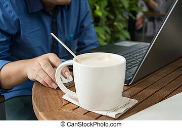 man with a cup of coffee working