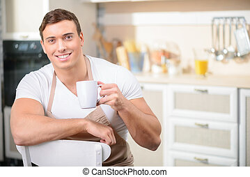Man with a cup of drink in the kitchen.