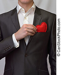 Man with a decorative heart - Man puts a red decorative...