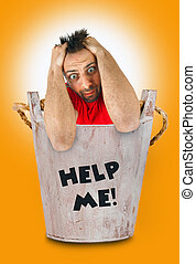 Man with a desperate expression in wooden bucket. - Young...