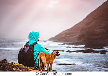 Man with a dog in front of rural coastline landscape with mountains and waves and sun rays comming through the clouds. Santo Antao Island, Cape Verde