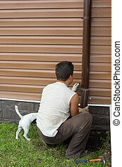 man with a dog sets drainpipe on the wall