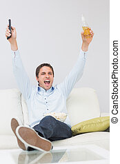 Man with a drink and remote control cheering on sofa