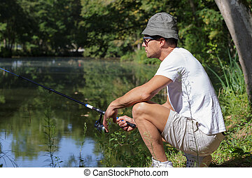 man with a fishing rod at the lake