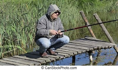 Man with a fishing rod on footbridg