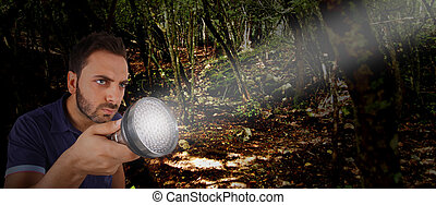 Man with a flashlight in the woods.