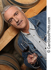 Man with a glass of red wine next to some barrels