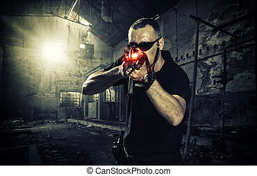 man with a gun and wearing sunglasses