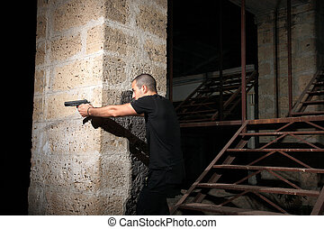 man with a gun in industrial place protect himself behind...