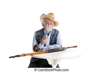 Man with a gun smokes a cigarette