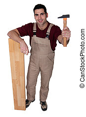 Man with a hammer and wooden floorboard
