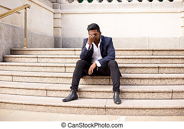 Man with a headache - young man sitting on steps in the...