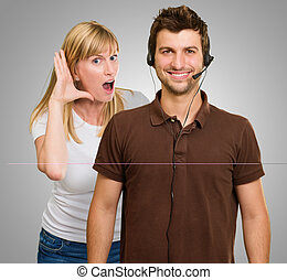 Man With A Headset And Woman Listening From Behind