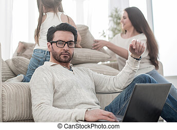 man with a laptop sitting in the living room