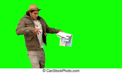 Man with a map and a compass orienteering on green screen in...