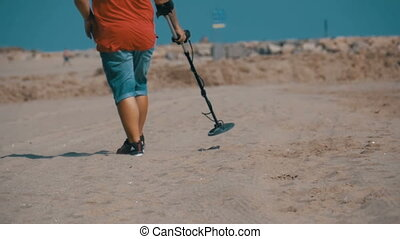Man with a Metal Detector Walks along a Sandy Beach on the...