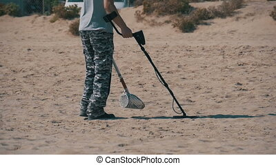 Man with a Metal Detector Walks along a Sandy Beach on the Seashore. Slow Motion