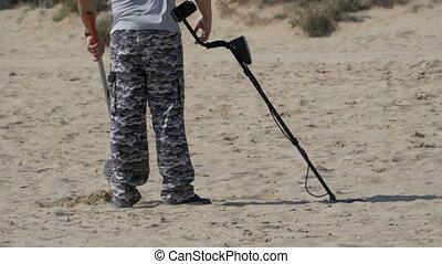 Man with a Metal Detector Walks along a Sandy Beach on the...
