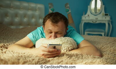 Man with a mobile phone in the morning lies on the bed, front view, lies in front of the camera