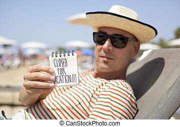 man with a note with the text closed for vacation