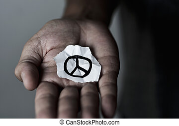 man with a peace symbol in a piece of paper
