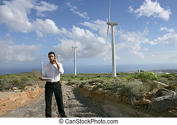 Man with a phone and laptop on a wind farm