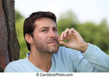 Man with a piece of grass in his mouth