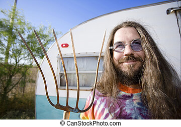 Man with a Pitchfork - Friendly Hippie with Long Hair and a...