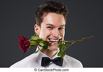 Man with a red rose in mouth