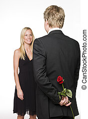 Man with a rose behind his back and a happy woman