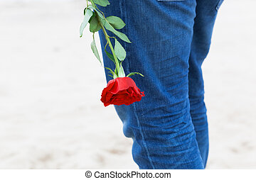 Man with a rose behind his back waiting for love. Romantic date on the beach