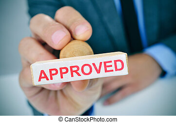 man with a rubber stamp with the word approved