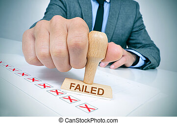 man with a rubber stamp with the word failed