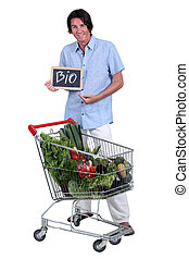 Man with a shopping trolley of organic produce