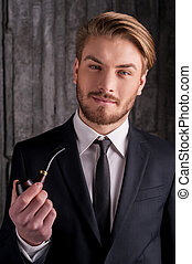 Man with a smoking pipe. Portrait of handsome young man in formalwear holding a smoking pipe and smiling at camera