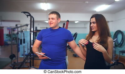 man with a tablet in the gym, she straightens her bra - man...