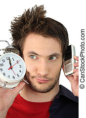 Man with alarm clock and mobile phone