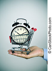 man with an alarm clock in a shopping cart