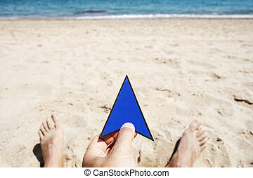 man with an arrow sign in his hand on the beach