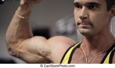 Man with an intense expression on his face training in the gym his biceps and triceps