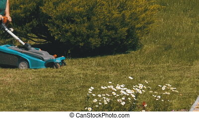 Man with an Portable Electric Lawnmower Mows the Green Grass on the Lawn in the Park