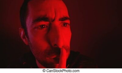 Man with angry facial expression make silence gesture. Close...
