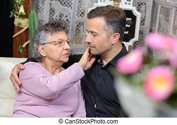 Man with arm around elderly woman