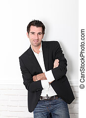 Man with arms crossed leaning on white wall