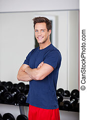 Man With Arms Crossed Standing In Gym