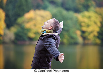 Man With Arms Outstretched Against Lake - Side view of...